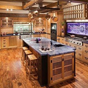 サンフランシスコの大きいアジアンスタイルのおしゃれなキッチン (エプロンフロントシンク、フラットパネル扉のキャビネット、淡色木目調キャビネット、木材カウンター、白いキッチンパネル、サブウェイタイルのキッチンパネル、シルバーの調理設備の、塗装フローリング、茶色い床) の写真