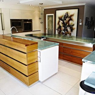 モントリオールの広いモダンスタイルのおしゃれなキッチン (アンダーカウンターシンク、フラットパネル扉のキャビネット、白いキャビネット、ガラスカウンター、シルバーの調理設備、セラミックタイルの床) の写真