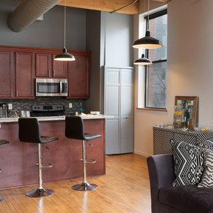 ミルウォーキーの大きいエクレクティックスタイルのおしゃれなキッチン (ラミネートカウンター、無垢フローリング、アンダーカウンターシンク、シェーカースタイル扉のキャビネット、中間色木目調キャビネット、黒いキッチンパネル、ボーダータイルのキッチンパネル、シルバーの調理設備の、茶色い床) の写真