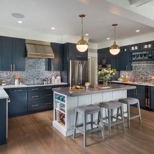 Maritim inredning av ett kök, med en undermonterad diskho, skåp i shakerstil, blå skåp, blått stänkskydd, rostfria vitvaror, mörkt trägolv och en köksö