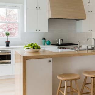 Inspiration for a mid-sized scandinavian galley light wood floor eat-in kitchen remodel in Boston with an undermount sink, flat-panel cabinets, white cabinets, gray backsplash, wood countertops, stainless steel appliances and ceramic backsplash