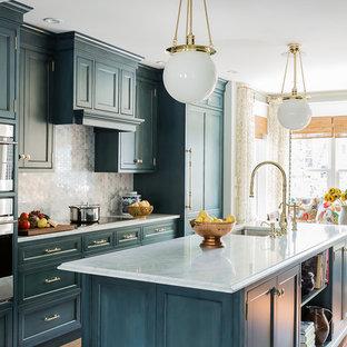 Inredning av ett klassiskt mellanstort kök och matrum, med en undermonterad diskho, luckor med profilerade fronter, blå skåp, marmorbänkskiva, grått stänkskydd, stänkskydd i stenkakel, integrerade vitvaror, mellanmörkt trägolv, en köksö och brunt golv
