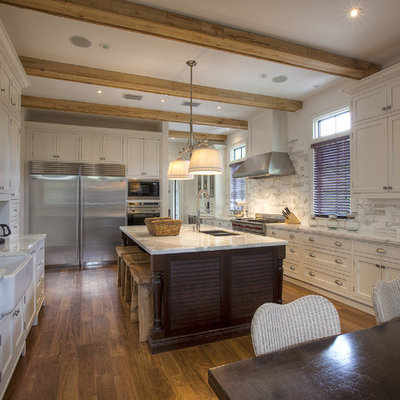 Example of an island style kitchen design in Miami with shaker cabinets, a farmhouse sink, white cabinets, marble countertops, white backsplash, stainless steel appliances and marble backsplash