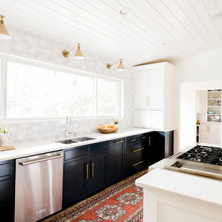 Midcentury kitchen in Atlanta with a double-bowl sink, shaker cabinets, black cabinets, multi-coloured splashback, stainless steel appliances, with island and white benchtop.
