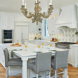 Traditional kitchen inspiration - Example of a classic l-shaped light wood floor kitchen design in Grand Rapids with white cabinets, quartz countertops, multicolored backsplash, ceramic backsplash, an island, shaker cabinets and paneled appliances
