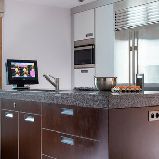 Small contemporary u-shaped enclosed kitchen in Other with flat-panel cabinets, white cabinets, granite worktops, metal splashback, stainless steel appliances, marble flooring, an island, brown floors and multicoloured worktops.