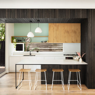 Photo of a contemporary galley kitchen in Melbourne with a double-bowl sink, flat-panel cabinets, white cabinets, green splashback, window splashback, medium hardwood floors, a peninsula, brown floor and white benchtop.