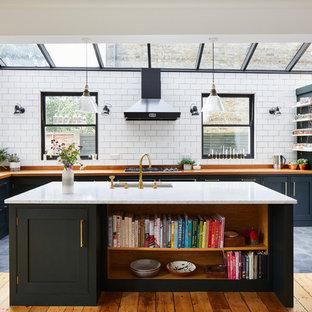 Diseño de cocina en L, clásica renovada, con fregadero bajoencimera, armarios estilo shaker, puertas de armario negras, encimera de zinc, salpicadero blanco, salpicadero de azulejos tipo metro, una isla, suelo gris y encimeras marrones