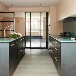 Moderne Küche mit flächenbündigen Schrankfronten, schwarzen Schränken, Küchenrückwand in Grün, hellem Holzboden, grauem Boden und grüner Arbeitsplatte in London