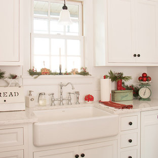 Inredning av ett lantligt litet parallellkök, med en rustik diskho, vita skåp, tegelgolv, skåp i shakerstil och marmorbänkskiva
