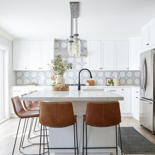 Mid-sized farmhouse kitchen designs - Kitchen - mid-sized cottage l-shaped laminate floor and brown floor kitchen idea in Los Angeles with white cabinets, multicolored backsplash, ceramic backsplash, an island, a farmhouse sink, shaker cabinets, stainless steel appliances and white countertops