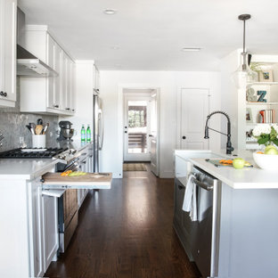 Small midcentury single-wall eat-in kitchen in Dallas with a farmhouse sink, flat-panel cabinets, white cabinets, granite benchtops, grey splashback, granite splashback, black appliances, dark hardwood floors, with island, brown floor and white benchtop.