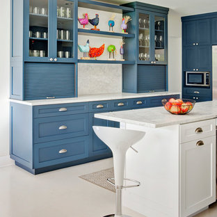 Photo of a mid-sized traditional u-shaped eat-in kitchen in Chicago with shaker cabinets, blue cabinets, white splashback, stone slab splashback, with island, marble benchtops, stainless steel appliances and vinyl floors.