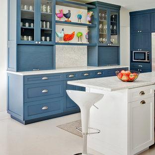 На фото: п-образная кухня среднего размера в классическом стиле с фасадами в стиле шейкер, синими фасадами, белым фартуком, фартуком из каменной плиты, островом, обеденным столом, мраморной столешницей, техникой из нержавеющей стали и полом из винила с