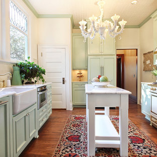 Example of an ornate galley medium tone wood floor enclosed kitchen design in Portland with a farmhouse sink, green cabinets, recessed-panel cabinets, quartz countertops, beige backsplash, ceramic backsplash and an island