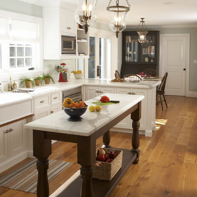 Eat-in kitchen - mid-sized traditional l-shaped medium tone wood floor eat-in kitchen idea in San Francisco with white cabinets, marble countertops, stainless steel appliances, white backsplash, ceramic backsplash, an island, a farmhouse sink and shaker cabinets