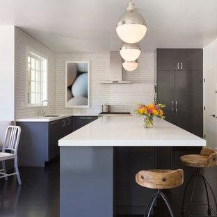 Стильный дизайн: большая п-образная кухня в современном стиле с белым фартуком, островом, обеденным столом, врезной раковиной, плоскими фасадами, серыми фасадами, техникой из нержавеющей стали и темным паркетным полом - последний тренд