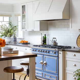 Design ideas for a classic u-shaped kitchen/diner in San Francisco with a belfast sink, shaker cabinets, white cabinets, engineered stone countertops, white splashback, ceramic splashback, stainless steel appliances, light hardwood flooring and an island.