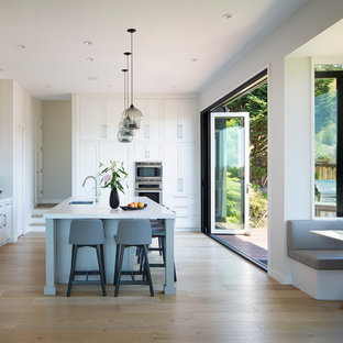 Photo of a large transitional l-shaped eat-in kitchen in San Francisco with an undermount sink, shaker cabinets, white cabinets, soapstone benchtops, white splashback, stone slab splashback, light hardwood floors, with island, beige floor, white benchtop and stainless steel appliances.