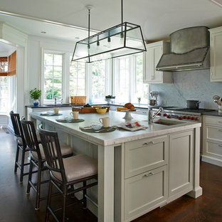 Traditional kitchen appliance - Example of a classic l-shaped dark wood floor kitchen design in New York with an undermount sink, shaker cabinets, gray cabinets, white backsplash, stone slab backsplash, stainless steel appliances and an island