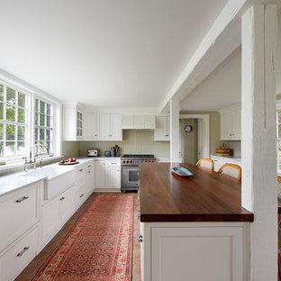 ボルチモアの広いトラディショナルスタイルのおしゃれなキッチン (エプロンフロントシンク、レイズドパネル扉のキャビネット、白いキャビネット、木材カウンター、白いキッチンパネル、シルバーの調理設備、レンガの床、赤い床、木材のキッチンパネル) の写真