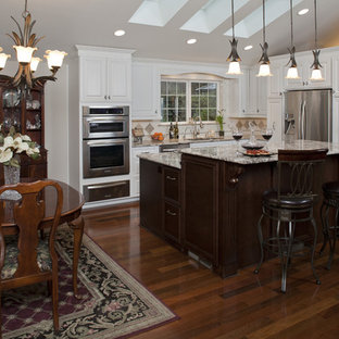 Example of a small classic l-shaped dark wood floor and brown floor eat-in kitchen design in Seattle with an undermount sink, raised-panel cabinets, white cabinets, granite countertops, beige backsplash, ceramic backsplash, stainless steel appliances and an island