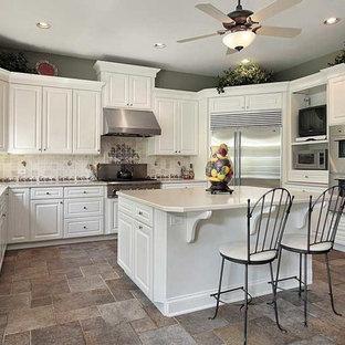 Klassisk inredning av ett vit vitt u-kök, med en dubbel diskho, luckor med upphöjd panel, vita skåp, beige stänkskydd, stänkskydd i stenkakel, rostfria vitvaror, tegelgolv, en köksö och grått golv