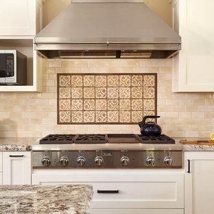 Example of a large classic l-shaped medium tone wood floor and brown floor open concept kitchen design in San Francisco with a farmhouse sink, shaker cabinets, white cabinets, granite countertops, beige backsplash, ceramic backsplash, stainless steel appliances and an island