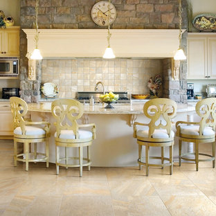 Large traditional l-shaped open plan kitchen in Boston with raised-panel cabinets, granite benchtops, beige splashback, ceramic splashback, stainless steel appliances, porcelain floors, with island, an undermount sink, beige cabinets and beige floor.