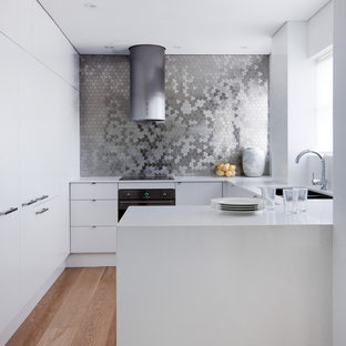This is an example of a small contemporary u-shaped eat-in kitchen in Sydney with metal splashback, black appliances, a drop-in sink, flat-panel cabinets, white cabinets, quartz benchtops and medium hardwood floors.