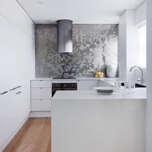 Foto di una piccola cucina contemporanea con paraspruzzi con piastrelle di metallo, elettrodomestici neri, lavello da incasso, ante lisce, ante bianche, top in quarzo composito e pavimento in legno massello medio