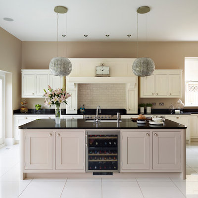 Large transitional single-wall open concept kitchen photo in London with shaker cabinets, beige cabinets, granite countertops, beige backsplash, subway tile backsplash, stainless steel appliances, an island and an undermount sink