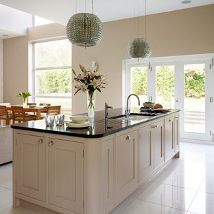 This is an example of a large contemporary single-wall open plan kitchen in London with shaker cabinets, beige cabinets, granite worktops, metro tiled splashback, stainless steel appliances and an island.