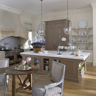 Design ideas for an expansive traditional l-shaped eat-in kitchen in Miami with stainless steel appliances, an undermount sink, recessed-panel cabinets, marble benchtops, light hardwood floors, with island, beige cabinets and grey splashback.