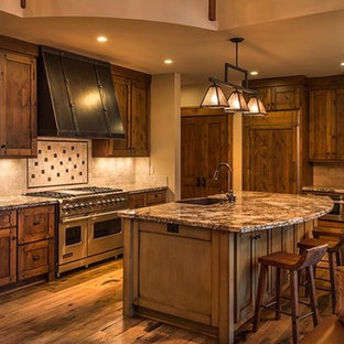 Mid-sized rustic eat-in kitchen appliance - Example of a mid-sized mountain style single-wall dark wood floor eat-in kitchen design in Seattle with an undermount sink, recessed-panel cabinets, dark wood cabinets, granite countertops, beige backsplash, stone tile backsplash, paneled appliances and an island
