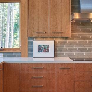 オレンジカウンティの広いコンテンポラリースタイルのおしゃれなキッチン (ドロップインシンク、フラットパネル扉のキャビネット、淡色木目調キャビネット、御影石カウンター、グレーのキッチンパネル、サブウェイタイルのキッチンパネル、シルバーの調理設備、セラミックタイルの床) の写真