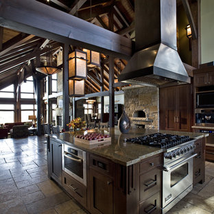 Idée de décoration pour une grande cuisine ouverte craftsman en U avec un évier de ferme, un placard à porte shaker, des portes de placard en bois sombre, un sol en travertin et un îlot central.