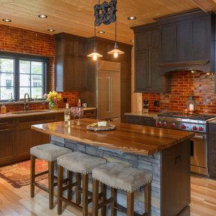 ボストンの中サイズのラスティックスタイルのおしゃれなキッチン (アンダーカウンターシンク、シェーカースタイル扉のキャビネット、濃色木目調キャビネット、シルバーの調理設備の、淡色無垢フローリング、御影石カウンター、茶色いキッチンパネル、レンガのキッチンパネル、ベージュの床) の写真