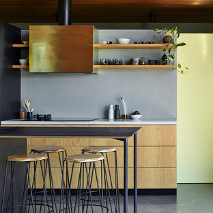 This is an example of a mid-sized industrial galley kitchen in Adelaide with flat-panel cabinets, light wood cabinets, cement tile splashback and with island.
