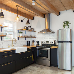 This is an example of a country l-shaped kitchen in Portland with a farmhouse sink, flat-panel cabinets, black cabinets, wood benchtops, white splashback, subway tile splashback, stainless steel appliances, concrete floors, no island and grey floor.