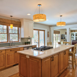 Design ideas for a mid-sized eclectic u-shaped eat-in kitchen in Detroit with an undermount sink, flat-panel cabinets, light wood cabinets, quartz benchtops, blue splashback, glass tile splashback, stainless steel appliances, medium hardwood floors and with island.