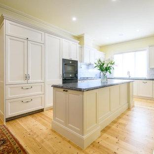 メルボルンの中くらいのトラディショナルスタイルのおしゃれなキッチン (ダブルシンク、落し込みパネル扉のキャビネット、白いキャビネット、御影石カウンター、白いキッチンパネル、セラミックタイルのキッチンパネル、黒い調理設備、淡色無垢フローリング、黄色い床、黒いキッチンカウンター) の写真
