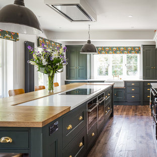 Large classic u-shaped kitchen in Manchester with shaker cabinets, green cabinets, granite worktops, white splashback, limestone splashback, an island, white worktops, a belfast sink, medium hardwood flooring and brown floors.
