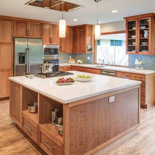Idéer för mellanstora amerikanska kök, med en undermonterad diskho, skåp i shakerstil, skåp i ljust trä, bänkskiva i kvarts, blått stänkskydd, stänkskydd i glaskakel, rostfria vitvaror, ljust trägolv, en köksö och brunt golv