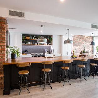 Zweizeilige, Geräumige Industrial Wohnküche mit Doppelwaschbecken, Schrankfronten mit vertiefter Füllung, schwarzen Schränken, Arbeitsplatte aus Holz, Küchenrückwand in Schwarz, Rückwand aus Metrofliesen, schwarzen Elektrogeräten, Kücheninsel, grauem Boden und weißer Arbeitsplatte in Brisbane