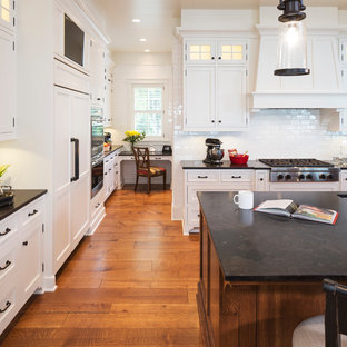 Large classic l-shaped open plan kitchen in Minneapolis with a submerged sink, flat-panel cabinets, white cabinets, granite worktops, white splashback, ceramic splashback, integrated appliances, an island, medium hardwood flooring, brown floors and black worktops.