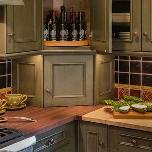 Kleine Landhausstil Wohnküche in L-Form mit Landhausspüle, flächenbündigen Schrankfronten, grünen Schränken, Kalkstein-Arbeitsplatte, bunter Rückwand, Rückwand aus Porzellanfliesen, Küchengeräten aus Edelstahl, braunem Holzboden, Kücheninsel und braunem Boden in Chicago