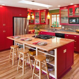 Klassische Küche in L-Form mit Doppelwaschbecken, Schrankfronten im Shaker-Stil, roten Schränken, Küchenrückwand in Grau, Küchengeräten aus Edelstahl, hellem Holzboden, Kücheninsel und Arbeitsplatte aus Holz in Sonstige