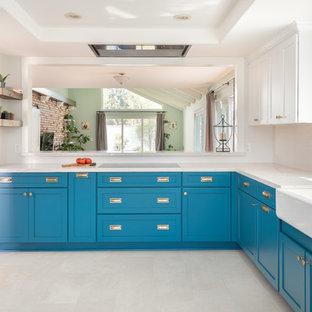 Esempio di una cucina ad U tradizionale con lavello stile country, ante in stile shaker, ante turchesi, elettrodomestici in acciaio inossidabile, pavimento beige e top beige