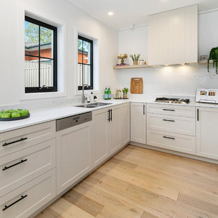 This is an example of a small transitional l-shaped open plan kitchen in Sydney with a double-bowl sink, white cabinets, marble benchtops, marble splashback, stainless steel appliances, light hardwood floors, white benchtop, recessed-panel cabinets, white splashback, multiple islands and brown floor.